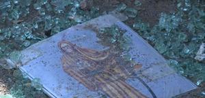 Una estampa de la Santa Muerte se aprecia entre los vidrios destrozados.