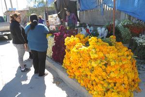 Vendedores de flores se colocaron a las afueras de los cementerios.