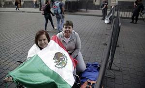 Mujeres permanecen en las calles del Zócalo a la espera de la llegada del papa.