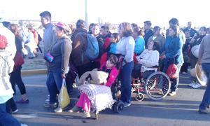 Niños en sillas de ruedas, adultos mayores se encuentran entre los asistentes.