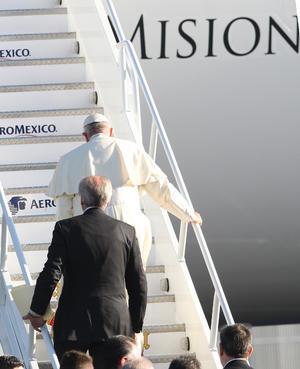 Al pie de la escalinata del avión, el papa estrechó la mano de las autoridades y, tras subir las escaleras, bendijo la aeronave con agua.
