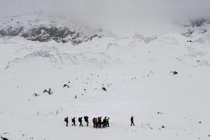 """Serie ganadora del segundo premio en """"Historias"""" de la categoría de deportes de la 59 edición del World Press Photo, tomada por el fotógrafo colombiano Roberto Schmidt. La fotografía muestra a un grupo de sherpas portando el cuerpo de un superviviente tras el desprendimiento de roca, hielo y nieve que acabó con la vida de más de 22 personas en el Everest, en el Himalaya, el 25 de abril 2015."""