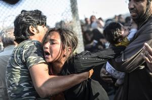 """Fotografía de la serie ganadora del tercer premio en """"Historias"""" de la categoría de noticias puntuales de la 59 edición del World Press Photo, tomada por el fotógrafo turco Bulent Kilic. La fotografía muestra a varias familias sirias intentando a cruzar la frontera turca cerca de la ciudad de Akçakale (Turquía) el 15 de junio de 2015."""