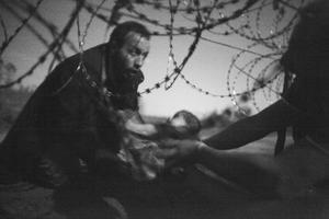 """La """"World Press Photo del Año"""" es una fotografía del australiano Warren Richardson, en blanco y negro, en la que se observa cuando un hombre, con los ojos fijos en el horizonte, pasa a un bebé debajo de una cerca de alambre de púas en la frontera entre Hungría y Serbia, bajo la luz de la Luna."""