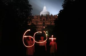 """Por la Tierra. Activistas forman con luces """"60+"""", simbólo de la Hora del Planeta, afuera del Monasterio Budista de Borobudur en Magelang, Java Central, Indonesia. En cada ciudad se apagaron las luces por una hora, 20:30 a 21:30 de la hora local."""