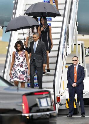 La lluvia acompañó la llegada de Obama y su familia a la isla, por lo que tuvieron que bajar las escalerillas del avión con paraguas negros.