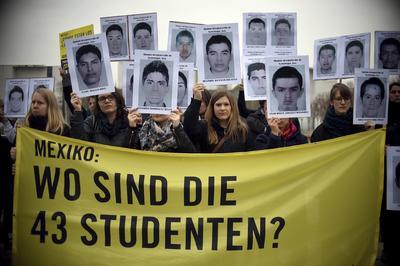 """Activistas de Amnistía Internacional sostienen una pancarta que lee """"México: ¿Dónde están los 43 estudiantes?"""" durante una protesta contra la tortura y las desapariciones en México con motivo de la visita del presidente de México, Enrique Peña Nieto, en Berlín."""