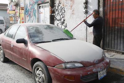 La población salió a limpiar sus vehículos de la ceniza.