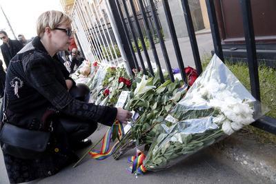 Una mujer deposita flores delante de la embajada estadounidense en Moscú, Rusia.