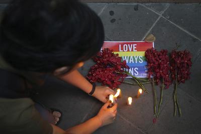 Un hombre enciende una vela en memoria de las victimas del ataque en la discoteca gay en Orlando ayer, en las puertas de la Embajada estadounidense en Bangkok, Tailandia.