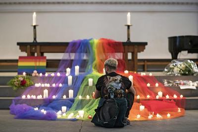 Varias personas depositan velas durante una vigilia por las 49 víctimas mortales, la mayoría hispanas, de la matanza perpetrada el pasado fin de semana en una discoteca de ambiente gay, celebrada en una iglesia de Zúrich, Suiza.