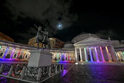 Las columnas de la Piazza del Plebiscito en Nápoles, Italia,  se iluminan con los colores del arcoíris.