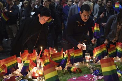 Varias personas participan en una vigilia en recuerdo a las víctimas de la matanza en una discoteca gay de Orlando, en la plaza Taylor, en Sídney, Australia.