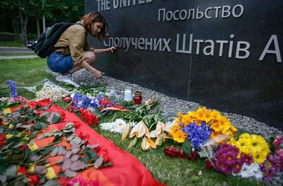 Una mujer enciende una vela en homenaje a las víctimas del tiroteo masivo en Orlando rente a la embajada estadounidense en Kiev, Ucrania.