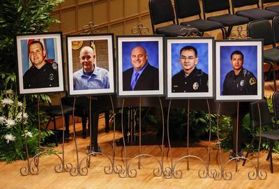DALLAS (TX, EE.UU.), .- Los retratos de los 5 policías muertos se exhiben hoy, martes 12 de julio de 2016, en un homenaje interreligioso en el Morton H. Meyerson Symphony Center en Dallas (TX, EE.UU.). Cinco policías perdieron la vida en una emboscada por un francotirador durante una protesta en Dallas el 7 de julio.