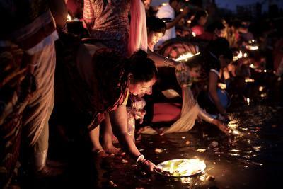 """DACA (BANGLADESH).- Varias fieles hindúes colocan sus velas sobre el agua para que sean arrastradas por la corriente al final del ritual Puyá (""""Bipodnashini Puja"""") celebrado en las calles de la parte antigua de Daca, Bangladesh hoy, 12 de julio de 2016. La comunidad hindú organiza cada año este ritual para protegerse del mal y del peligro."""