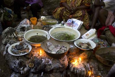Creyentes vudú calientan hojas aromáticas antes de bañarse en una cascada que creen tiene poderes de purificación durante la celebración anual de Saut d' Eau.