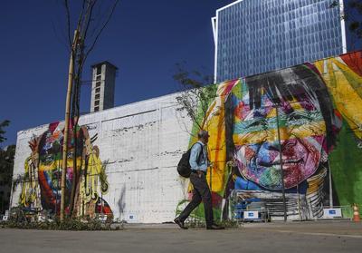 Un hombre camina frente a uno de los rostros de un mural gigante, este viernes, 15 de julio de 2016, en Río de Janeiro (Brasil). Un gigantesco mural de 3.000 metros cuadrados en el que destacan los rostros de representantes de etnias de los cinco continentes es el regalo del reconocido grafitero brasileño Eduardo Kobra a Río de Janeiro con motivo de los Juegos Olímpicos de agosto próximo.