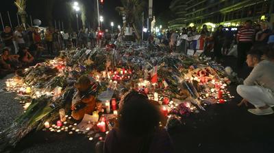 Flores y velas tributo se colocan cerca del lugar del ataque camión en la turística  ciudad francesa de Niza, la madrugada del domingo.