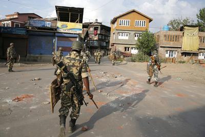 Soldados paramilitares indios caminan de regreso hacia su campamento durante el toque de queda en Srinagar, capital de la Cachemira india