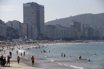 Turistas disfrutan la playa Copacabana en Río de Janeiro (Brasil). La caída del dólar y el aumento de precio de algunos servicios, como los hoteles, encarecerán la ciudad brasileña de Río de Janeiro durante los Juegos Olímpicos de agosto, aunque los turistas la encontrarán más accesible económicamente que durante el Mundial de fútbol 2014.