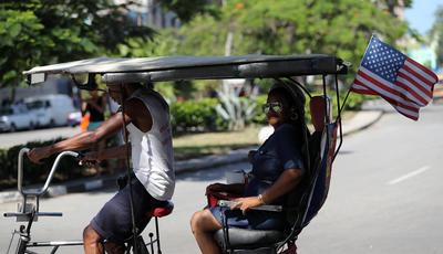 Un bicitaxi con una bandera de Estados Unidos circula en La Habana (Cuba).