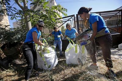 Activistas palestinos, israelíes y estadounidenses realizan labores de limpeza en los alrededores de casas palestinas en Tal Rumaida, en la ciudad de Hebrón.