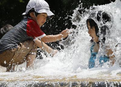 Los niños juegan en la fuente de agua en el parque de Asuka en Tokio.