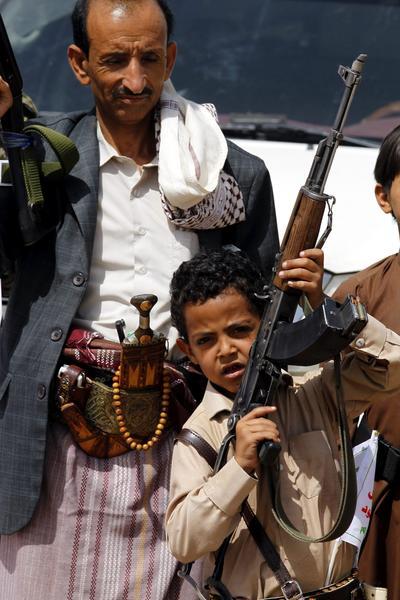 Un niño levanta un arma durante una reunión de los rebeldes hutíes para movilizar a más combatientes para hacer frente a las fuerzas del presidente Hadi, en Saná, Yemen.
