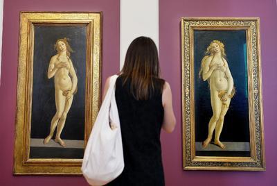 """Una mujer contempla las dos venus del artista italiano Sandro Botticelli (1445-1510) durante un pase para la prensa antes de la inauguración de la exposición """"Venus conoce a Venus""""."""