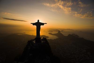 El sol se levanta detrás de la estatua del Cristo Redentor, por encima de la bahía de Guanabara en Río de Janeiro, Brasil.