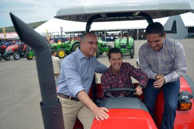 El presidente de México, Enrique Peña Nieto (c), el secretario de Agricultura, José Calzada (i), y el gobernador de Michoacán, Silvano Aureoles (d), montan en un tractor en el municipio de Charo.