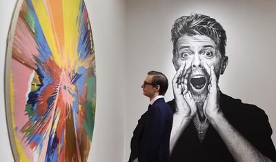 Un visitante a Sotheby's mira una de las famosas pinturas giratorias de Damien Hirst la cual pertenece a la colección privada de arte del artista David Bowie en la sede de la casa de subastas en Londres, Reino Unido.