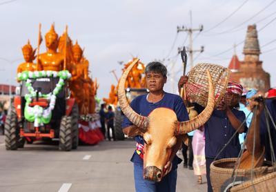 """Varios granjeros desfilan delante de un tractor que carga varias figuras de la mitología del budismo realizadas en cera durante una marcha que conmemora el inicio de la """"cuaresma"""" del Budismo en la provincia de Suphan Buri, Tailandia."""