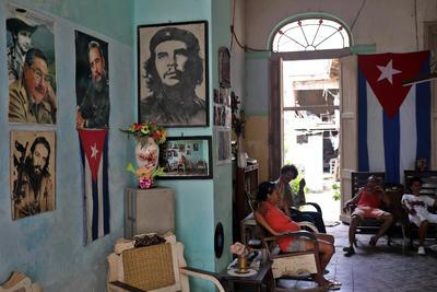 Varias personas permanecen en la sala de una casa decorada con imágenes de líderes de la revolución cubana, en La Habana (Cuba).