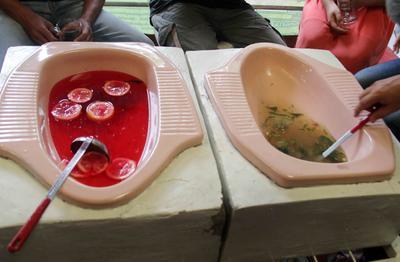La Fotografía muestra a los visitantes que toman sus bebidas servidas de tazas de inodoro en 'Jamban Cafe' (Inodoro Cafe) en Semarang, Java Central, (Indonesia).
