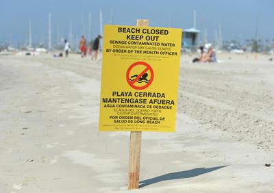 Un letrero en la playa de Alamitos advierte sobre los peligros de las aguas residuales contaminadas, en Long Beach, California.
