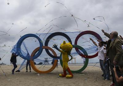 Un grupo de personas junto a Vinicius (c) la mascota de los juegos, lanzan serpentinas durante la inauguración de los anillos olímpicos en la playa de Copacabana, Río de Janeiro (Brasil) a 15 días del comienzo de los Juegos Olímpicos de Río 2016.