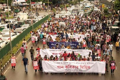 Activistas culturales de Bangladesh asisten a la celebración de una marcha portando fotos de extranjeros muertos junto con canciones y poemas contra todo terrorismo en todo el mundo organizada por Shommilito Shangskritik Jote en Dhaka.