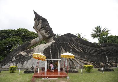 Un residente de Lao pone un ofrenda a una estatua gigante de Buda reclinado en el Parque de Buda Xiengkuane en Vientiane.