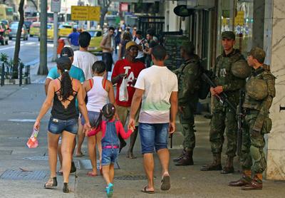 Integrantes de las Fuerzas Armadas brasileñas vigilan en la playa de Copacabana hoy, en Río de Janeiro (Brasil). Las calles de Río de Janeiro, la ciudad que el próximo agosto acogerá los Juegos Olímpicos, amanecieron hoy con militares de las Fuerzas Armadas brasileñas, quienes reforzarán la seguridad durante la competición deportiva.