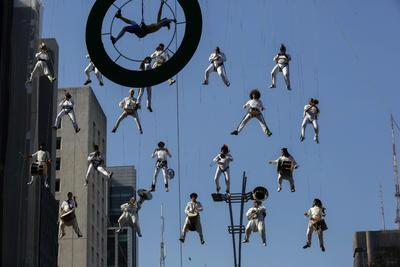 Una banda de músicos suspendidos en el aire con cables anima el recorrido de la llama olímpica, por la Avenida Paulista en Sao Paulo (Brasil).