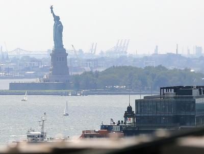 Imagen de la Estatua de la Libertad envuelta en bruma en el puerto de Nueva York, en esta vista desde el puente de Brooklyn.