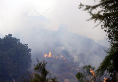 Un helicóptero de extinción de incendios se envuelto en humo mientras lucha contra el fuego de la arena en Santa Clarita, California, EE.UU. Los informes indican que el fuego ha quemado al menos 18 estructuras y mató a una persona cerca de Los Ángeles.