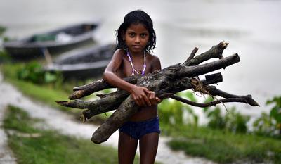 Una niña carga con varios troncos de madera que ha recogido en una zona inundada en el distrito de Morigaon, en el estado indio de Assam.