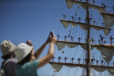Dos personas sacan fotos de los marineros sobre el mástil del barco mexicano Cuauhtemoc mientras permanece atracado en el muelle de Santa Apolonia, durante la Regata de Grandes Veleros de Lisboa, en Portugal.