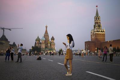Una joven mujer sostiene a su teléfono inteligente en la Plaza Roja con la Torre Spasskaya del Kremlin, a la derecha, y la catedral de San Basilio, centro, en el fondo, en Moscú.