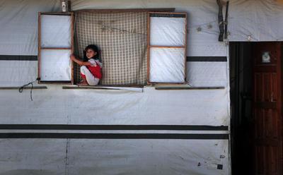 Una niña palestina está sentada en el alféizar de la ventana de la casa de su familia en la localidad de Juzaa, al sur de la Franja de Gaza.