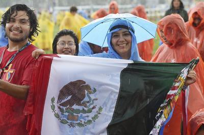Una peregrina sostiene bajo la lluvia la bandera nacional de México durante la XXXI Jornada Mundial de la Juventud (JMJ) en Cracovia, Polonia.