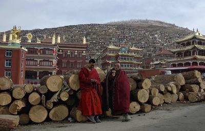 Fotografía facilitada, que muestra a dos monjes sentados cerca de los principales edificios de la escuela budista de Larung Gar en Seda, provincia de Sichuan, China.